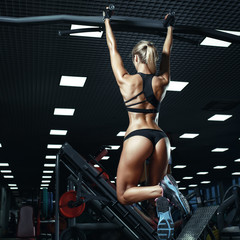 Sexy hot blonde fitness bikini girl with perfect shape body making elevations pull up in gym