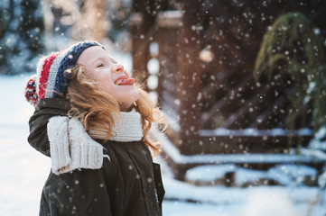 happy child girl catching snowflakes and playing on winter snowy walk in garden, seasonal outdoor activities on vacations