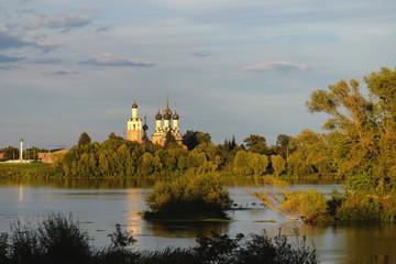 Православный храм на берегу реки в лучах закатного солнца