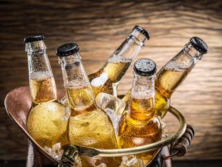 Cold bottles of beer in the brazen bucket.
