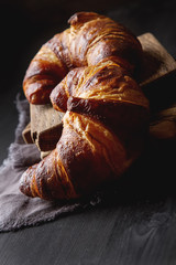 French food for breakfast. Fresh baked croissants. Dark wood bac