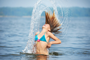 Girl teenager with splashes from hair on lake