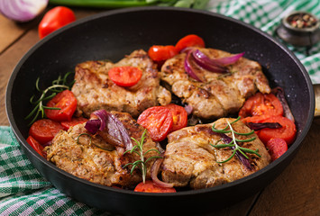 Juicy pork steak with rosemary and tomatoes on pan