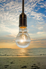 close up of vintage light bulb on background of sunset beach