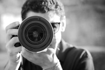 Ritratto di ragazzo che scatta fotografia con fotocamera reflex in bianco e nero