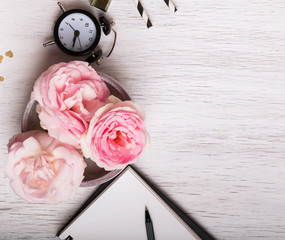 Beautiful pink roses and clock on white table