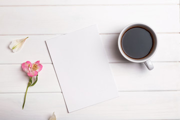Blank paper, coffee and flower on white table
