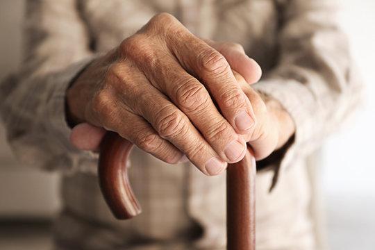 Old man hands on walking stick