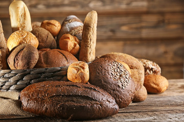 Many different types of fresh bread on old wooden table