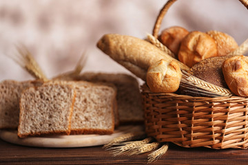Basket with fresh bread and slices with spikes on a wooden table