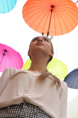 Girl posing under colorful umbrellas