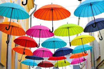 Multicolored umbrellas hanging on strings