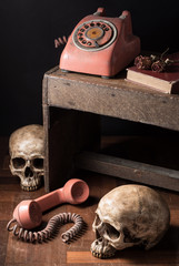 Still life photography : old telephone old book and dry rose with skull at foreground and background in nostalgia concept