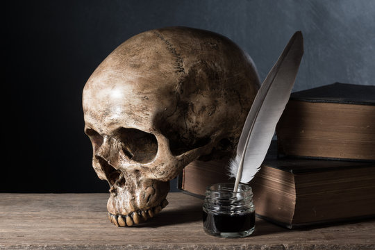 still life photography : skull with inkwell and old book on art dark background