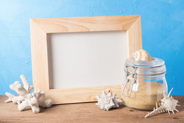 still life photography : handicraft wood frame with sand in glass jar, shell and coral on blue texture background in sea element concept