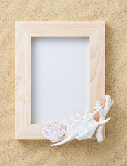 handicraft wood frame with shell and coral on sand texture background