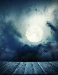 Halloween background. Spooky forest with full moon and wooden table, over light