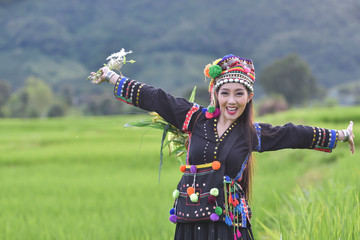 women wearing tribal costumes work in the fields of rice terraces .