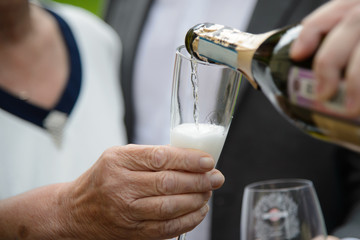 Hand of an old woman with a glass in which champagne is poured. Elderly people on holiday. Aged wrinkled hand.