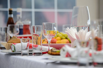 Served dishes to the table for the holiday. Cutlery and food on white tablecloths in the restaurant. Design a festive Banquet. Luxurious food for guests and visitors.
