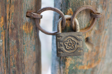 Old Rusty Decorated Padlock on a Wooden Door. Vintage Corroded Padlock on a Ancient Gate Background.
