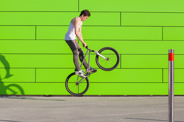 Boy on bike make the bunny hop trick at green wall background