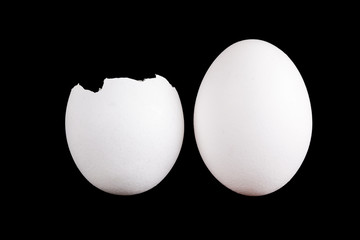 whole egg and empty eggshell isolated on black background