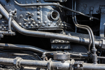 Detail of steam train engine; the strength and power of metal, engineering, coal and manpower for transporting passengers and goods across the USA.