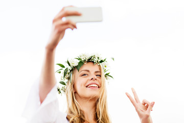woman taking smartphone selfie and showing peace