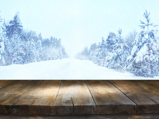 Empty wooden table in front of dreamy winter landscape