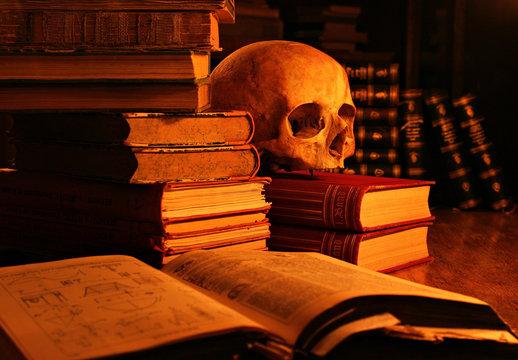 Memento Mori, Stillleben mit Totenschädel und alten Büchern, beleuchtet von Kerzenlicht