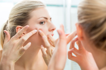 Blond woman squeezing pimples