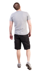Back view of walking handsome man in shorts and sneakers.   Sports-dressed young man moves. going young guy. Rear view people collection.  backside view of person.  Isolated over white background