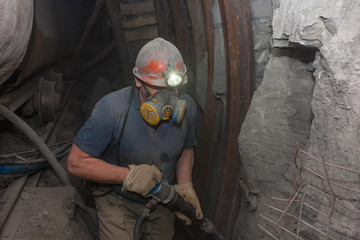 Miner in a respirator with a jackhammer in underground coal mine