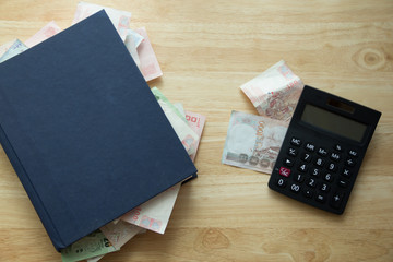 calculator with money in book,education make money,natural day light, selective focus, space for copy