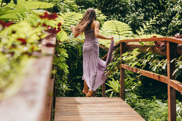 Woman in beautiful dress walking on wooden bridge in nature.