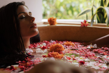 Young woman having flower bath