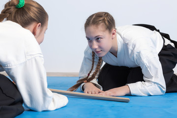Two girls in black hakama bow on Aikido training