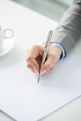Hand of business person writing new strategy on white sheet