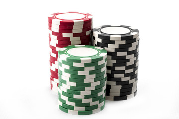 Three stacks of red, green and black casino chips isolated on white