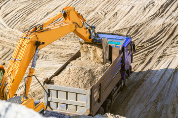 Excavator loading sand into dumper truck