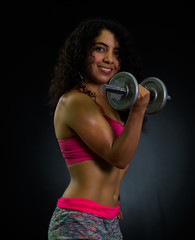 Athletic brunette woman wearing pink top and matching shorts, training with weights while posing for camera, black studio background