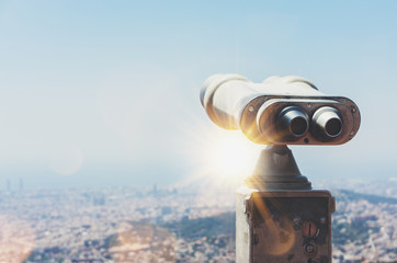Touristic telescope look at the city view of Barcelona, close up old metal binoculars background overlooking the mountain, hipster coin operated in panorama observation nature blue sky, mockup flare