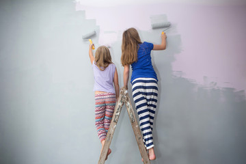 Girls paint wall at home.
