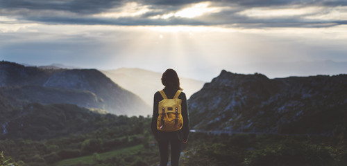 Hipster young girl with backpack enjoying sunset on peak mountain. Tourist traveler on background valley landscape view mockup. Hiker looking sunlight flare in trip in Spain basque country Europa Fotomurales