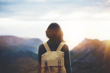 Hipster young girl with backpack enjoying sunset on peak mountain. Tourist traveler on background valley landscape view mockup. Hiker looking sunlight flare in trip in Spain basque country Europa Wall mural