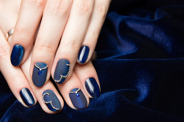 French manicure - beautiful manicured female hands with blue manicure with rhinestones on dark blue background