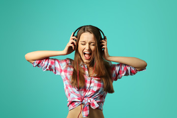 Young woman listening music on blue background.