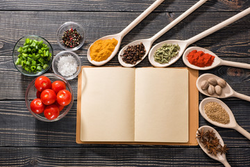 spices and open book of recipes on a dark wooden background, top