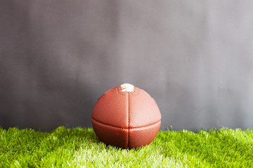 Vintage football over grass and black background